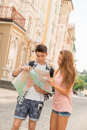 Photo for Waist-up portrait of a beautiful couple of tourists holding a map in their hands and both looking at the map and concentrated deciding where to go, concept of summer holidays and tourism - Royalty Free Image