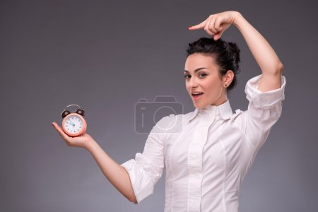 Portrait of pretty girl holding an alarm clock in her hand showi