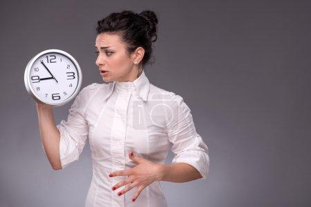 Afraid girl looking at the big clock