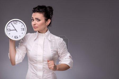 Afraid girl holding big clock