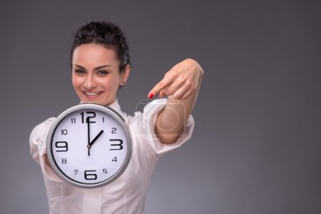 Photo for Waist-up portrait of beautiful smiling girl holding a big clock in her hands and looking at the camera, with selective focus on a clock isolated on grey background with copy place - Royalty Free Image