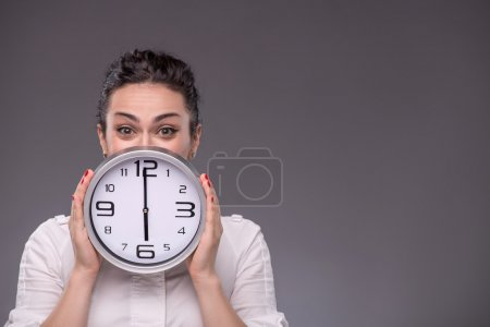 Photo for Close-up portrait of girl hiding her face with a big clock in her hands and looking at the camera, isolated on grey background with copy place concept of time management - Royalty Free Image