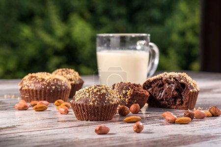 Photo pour Gros plan image tasse de lait et quatre cupcakes au chocolat l'un d'eux cassé décoré d'amandes et de noisettes sur une table en bois dans un café avec place de copie - image libre de droit