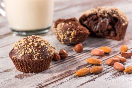 Photo pour Photo en gros plan avec mise au point sélective sur un seul cupcake, également tasse de lait et quatre cupcakes au chocolat l'un d'eux brisé décoré d'amandes et de noisettes sur une table en bois dans un café - image libre de droit