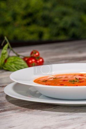 Photo pour Gros plan image basse-angle de gazpacho soupe tomate froid savoureux avec des espèces sur la table en bois dans un café végétalien avec des tomates debout près d'une assiette, avec place de copie et accent sélectif sur une assiette - image libre de droit
