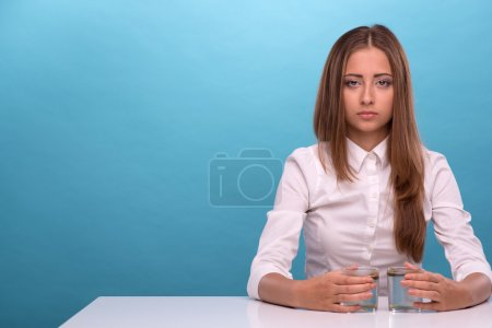 Young girl testing the quality of water in glasses