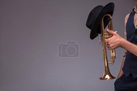 Photo pour Photo en gros plan d'une trompette avec un chapeau noir dans les mains d'un homme de jazz en costume isolé sur fond gris avec place de copie, concept de musique jazz - image libre de droit