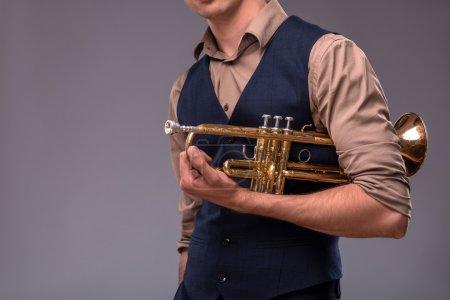 Photo pour Photo en gros plan d'une trompette dans les mains d'un homme de jazz en costume isolé sur fond gris avec lieu de copie, concept de musique jazz - image libre de droit