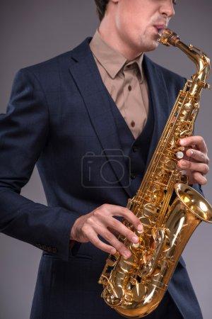 Photo pour Photo en gros plan d'une trompette dans les mains d'un homme de jazz en costume jouant dessus avec enthousiasme isolé sur fond gris avec lieu de copie, concept de musique jazz - image libre de droit
