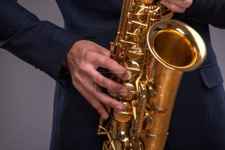 Photo pour Gros plan des mains d'un homme de jazz jouant avec enthousiasme sur une trompette en costume isolé sur fond gris avec lieu de copie, concept de musique jazz - image libre de droit