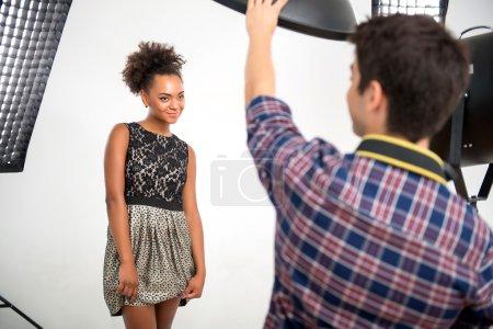 Photo pour Focus sélectif sur le charmant modèle africain souriant portant une magnifique robe de soirée debout devant des projecteurs regardant le photographe - image libre de droit