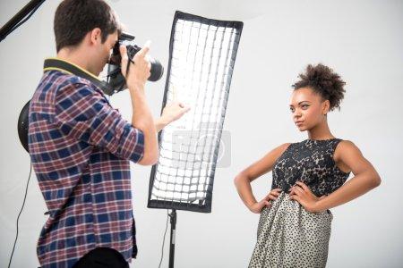 Photo pour Portrait à mi-longueur d'un charmant modèle africain portant une magnifique robe de soirée posant devant des projecteurs regardant le photographe - image libre de droit