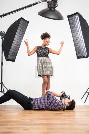 Photo pour Portrait intégral du beau modèle africain souriant portant une superbe robe de soirée debout devant les projecteurs parlant au beau photographe souriant portant une chemise à carreaux couchée sur le sol - image libre de droit