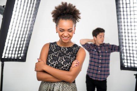 Photo pour Focus sélectif sur le joli modèle africain souriant portant une jolie robe de soirée debout dans le studio près des projecteurs qui sont mis à droite par le photographe en arrière-plan - image libre de droit