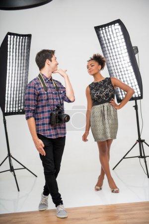 Photo pour Portrait complet de jeune beau photographe vêtu d'une chemise à carreaux debout devant les projecteurs enseignant à un jeune modèle africain comment poser - image libre de droit