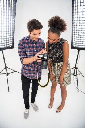 Photo pour Portrait complet d'une jeune belle photographe portant une chemise à carreaux debout entre les projecteurs avec la jeune mannequin africaine montrant ses photos - image libre de droit