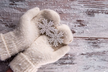 Photo for Christmas tree toys like silver snowflakes   in hands  dressing in white  mittens on wooden table top view with copy place - Royalty Free Image