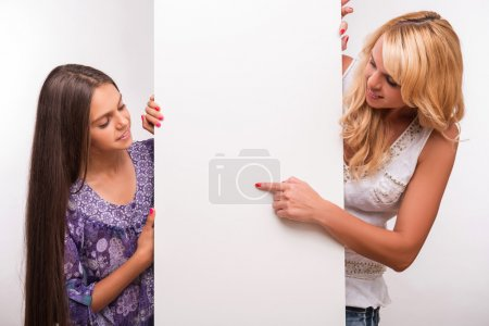 Photo for Young mother looking out wall and putting aside   and her   daughter teenager isolated on white background with copy place - Royalty Free Image