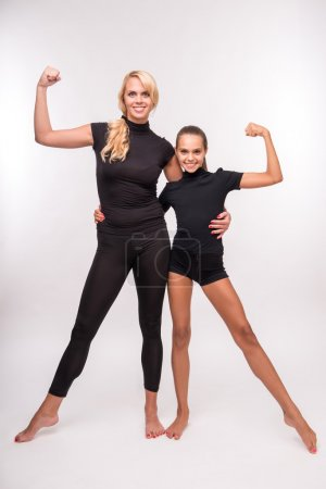 Photo for Young sport  mother and her   daughter teenager showing their  muscles looking at camera  isolated on white background - Royalty Free Image