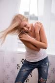 Blondýnka dotýká její ramena s rukama