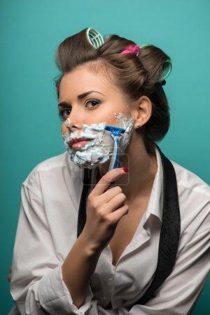 Photo pour Femme brune mignonne dans les bigoudis posant avec de la mousse sur le rasage du visage avec rasoir et penché vers l'avant, isolé sur fond bleu, concept de renversement du genre rôle - image libre de droit