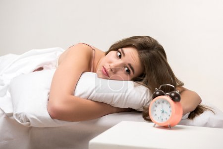 Photo for I need more time to sleep. Young woman looking at clock while lying in bed - Royalty Free Image