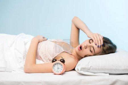 beauté, couché sur le lit avec une horloge