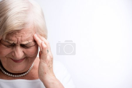 Photo for Suffering from severe headache. Closeup portrait of elderly woman touching her head with fingers suffering from terrible pain while standing against white background - Royalty Free Image
