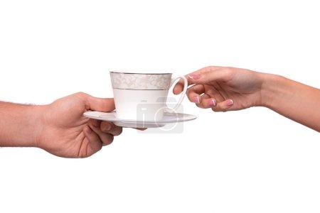 Main en donnant la tasse et soucoupe