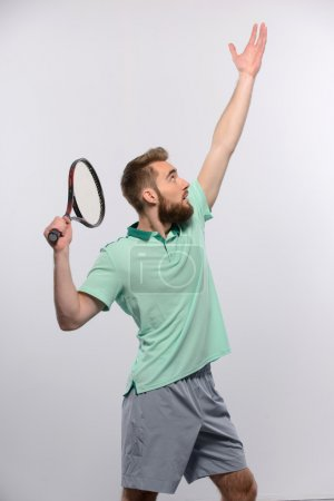 Photo for Ready to serve. Happy young man in polo shirt raising his tennis racket up while standing on against white background - Royalty Free Image