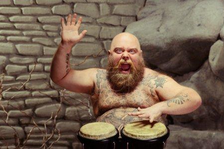 Photo pour La musique est son âme. Verticale d'homme torse nu barbu drôle avec le corps tatoué jouant le tambour avec l'inspiration tout en s'asseyant contre le fond de mur de pierre - image libre de droit