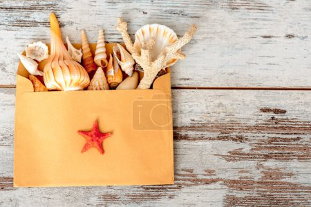 Photo for Memories that last forever. Romantic composition of craft paper envelope full of seashells, seastars and coral placed on wooden background - Royalty Free Image