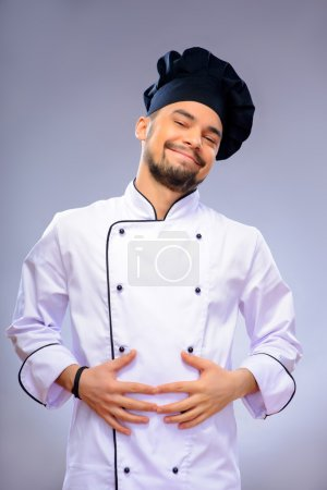Photo for My stomach is full.  Portrait of handsome cook keeping his hands on his stomach and smiling while standing against grey background with copy space - Royalty Free Image