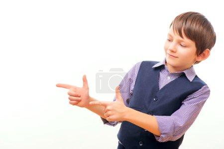 Foto de Bang bang. Primer plano de niño juguetón en ropa formal que muestra la pistola de dedo mientras está de pie aislado sobre fondo blanco con espacio de copia - Imagen libre de derechos