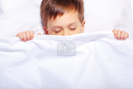 Boy sleeping under the blanket