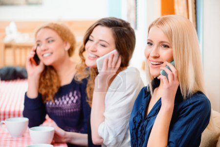 Women talking over their cell phones