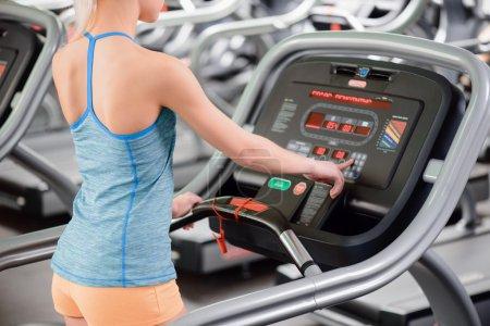 Photo pour Entraînement cardio. Vue arrière de jeune belle femme dans des vêtements de sport mettant en place son séance d'entraînement avant de courir sur un tapis roulant dans la gymnastique - image libre de droit