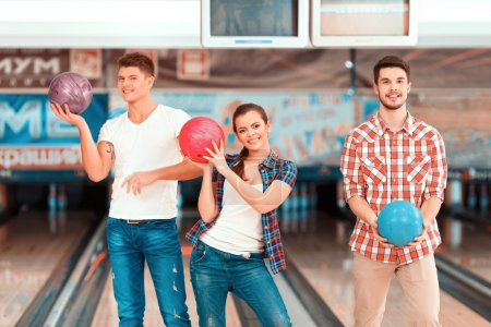 Young people holding bowling balls