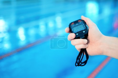 Photo for Stopwatch. Swimming coach looking at his stopwatch by the pool at the leisure center - Royalty Free Image