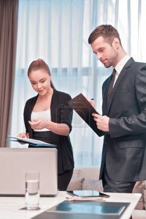 Photo for At the business meeting. Two cheerful business people in formal wear looking at the laptop together and pointing at something - Royalty Free Image