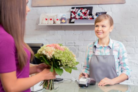 Photo pour Perfect choice.  Selective focus of a florist using a point of sale terminal for purchase of a bouquet which holds a client - image libre de droit