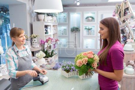 Photo pour Procédure de paiement facile. Conversation entre le client et le fleuriste faisant un achat par l'intermédiaire du terminal de point de vente - image libre de droit