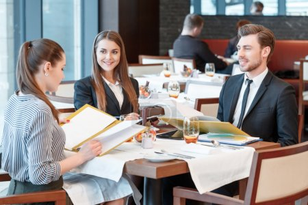 Photo for Business success is a good news. Business managers sitting at the lunch table smile to each other with delight - Royalty Free Image