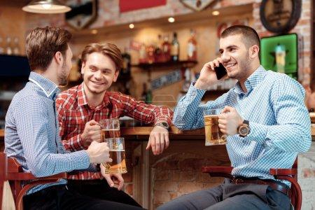 Photo pour Appel important au cours de la réunion avec des amis. Trois jeunes hommes assis au bar comptoir et boire de la bière pendant que l'un d'eux parle au téléphone - image libre de droit