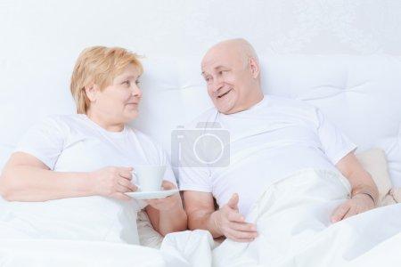 Photo pour Discussions du soir. Couples aînés dans les t-shirts blancs buvant le thé dans le lit avant d'aller dormir - image libre de droit