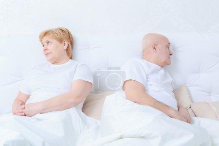 Photo pour Incompréhension. Le couple aîné triste et irrité se trouvant dans le lit regarde à part comme si avoir une querelle - image libre de droit