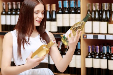 Woman holds a wine bottle in the store