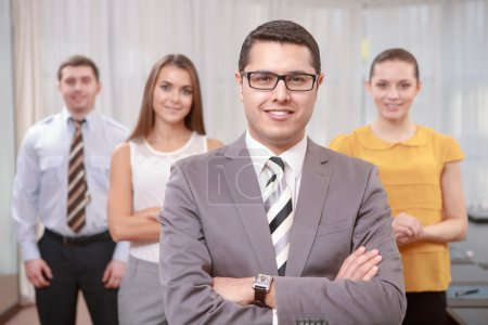 Photo for Real leader. Young handsome top manager wearing suit and tie standing with his arms crossed on a chest while his team stands smiling behind him - Royalty Free Image