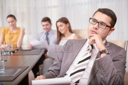Photo pour Réfléchir aux prochaines étapes. Gestionnaire concentré beau d'affaires touchant son menton avec la pensée de main au-dessus de l'information à la réunion - image libre de droit