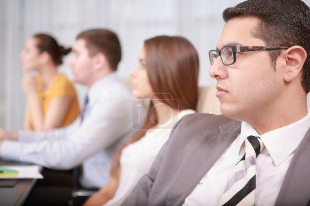 Photo pour Regarder la présentation. Beau directeur d'affaires réservé regardant droit devant s'asseyant avec ses collègues à la réunion d'affaires - image libre de droit